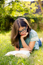 Girl lying on a meadow in garden reading book - LVF07895