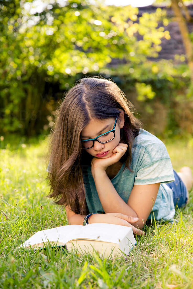 Girl lying on a meadow in garden reading book - LVF07895 - Larissa Veronesi/Westend61