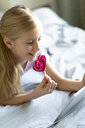 Smiling blond girl lying on bed with lollipop using digital tablet - JPF00369