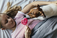 Girl lying on bed watching her dog licking lollipop - JPF00375
