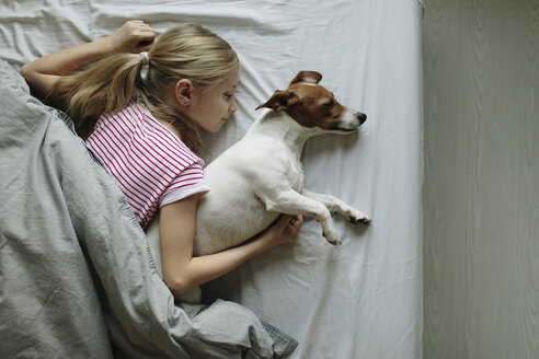 Blond girl lying on bed with her dog sleeping, top view - JPF00378