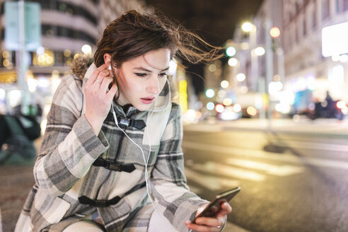 Spain, Madrid, young woman in the city at night next to Gran Via using her smartphone and wearing earphones - WPEF01397