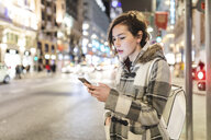 Spain, Madrid, young woman in the city at night using her smartphone - WPEF01400