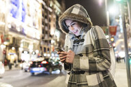 Spain, Madrid, young woman in the city at night next to Gran Via using her smartphone - WPEF01403