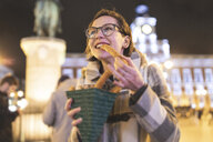 Spain, Madrid, young woman in the city at night eating typical churros with chocolate - WPEF01406