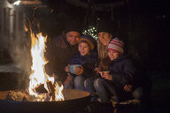 Family with mugs sitting at the fire at night - LBF02499