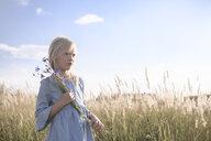 Blond girl holding cornflowers in a field - EYAF00038