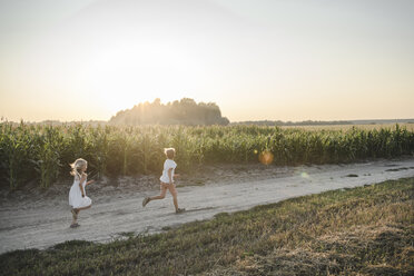 Girl and boy running on a rural dirt track along cornfield - EYAF00053