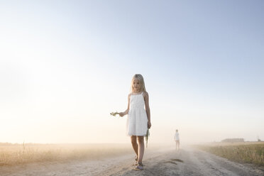 Girl walking on a rural dirt track - EYAF00056