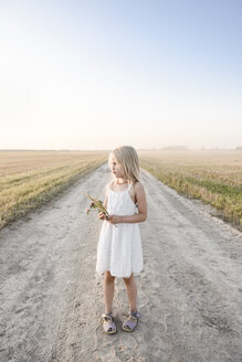 Girl standing on a rural dirt track - EYAF00059