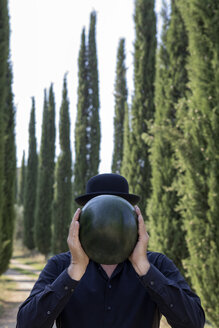Italy, Tuscany, man surrounded by cypresses wearing a bowler hat holding a melon - PSTF00334