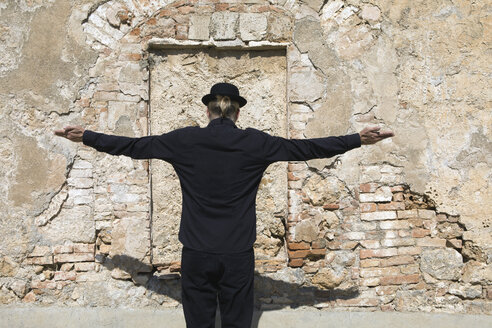 Rear view of man wearing a bowler hat standing at stone wall with arms outstretched - PSTF00346