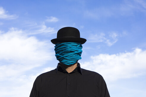 Man wearing bowler hat with rope wrapped around his face - PSTF00358
