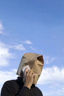 Man with paper bag above his head talking on cell phone - PSTF00361