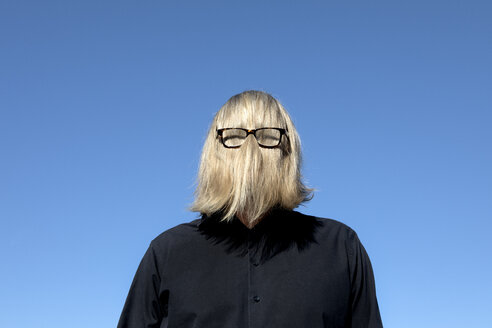 Blond hair covering man's face wearing glasses - PSTF00367