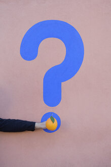 Man's hand holding an orange at a wall with question mark - PSTF00370