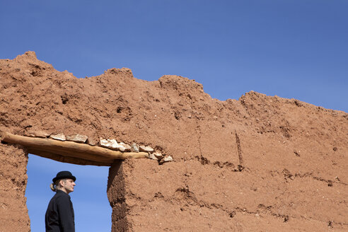 Morocco, Ait-Ben-Haddou, man wearing a bowler hat under loam wall - PSTF00373