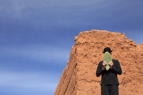 Morocco, Ait-Ben-Haddou, man wearing a bowler hat holding a cactus leaf in front of his face - PSTF00376