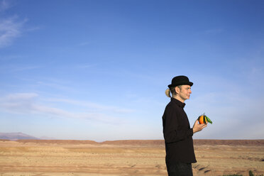 Morocco, Ounila Valley, man wearing a bowler hat holding an orange - PSTF00382