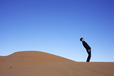 Morocco, Merzouga, Erg Chebbi, man wearing a bowler hat standing crooked on desert dune - PSTF00391