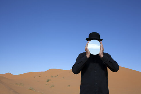 Morocco, Merzouga, Erg Chebbi, man wearing a bowler hat holding mirror in front of his face in desert dune - PSTF00394