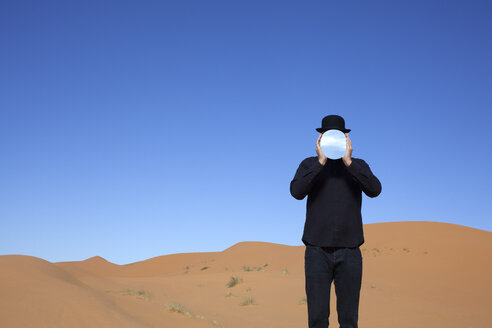 Morocco, Merzouga, Erg Chebbi, man wearing a bowler hat holding mirror in front of his face in desert dune - PSTF00397