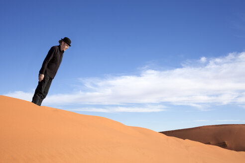 Morocco, Merzouga, Erg Chebbi, man wearing a bowler hat standing crooked on desert dune - PSTF00400