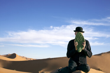 Morocco, Merzouga, Erg Chebbi, man wearing a bowler hat holding cactus leaf in front of his face in desert dune - PSTF00403