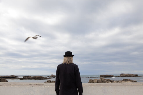 Morocco, Essaouira, rear view of man wearing a bowler hat standing at the sea - PSTF00418