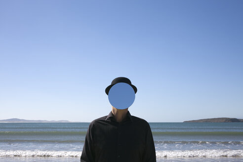Morocco, Essaouira, man wearing a bowler hat with mirror in front of his face at the sea - PSTF00424