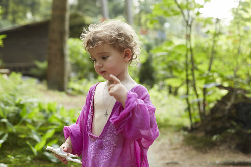 Little girl wearing pink tunic in nature holding horse figurine - AMEF00040