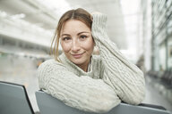 Portrait of smiling young woman at the airport sitting in waiting area - PNEF01367