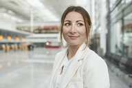 Portrait of smiling young businesswoman at the airport - PNEF01370