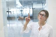 Young businesswoman touching virtual touchscreen - PNEF01376