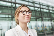 Portrait of young businesswoman wearing glasses in front of a building - PNEF01382