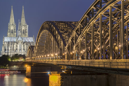 Germany, Cologne, view to lighted Cologne Cathedral with Hohenzollern Bridge in the foreground - MKFF00474