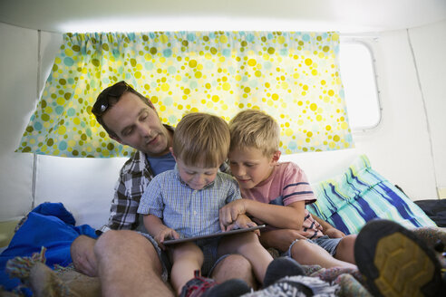 Father and sons using digital tablet inside camper - HEROF31041