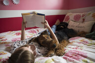 Dog laying on girl reading book on bed - HEROF31086