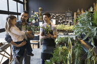 Male shop owner helping father and daughter shopping in plant shop - HEROF31165