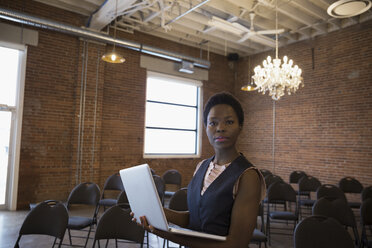 Portrait confident businesswoman with laptop preparing for meeting in conference room - HEROF31192