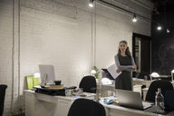 Portrait confident creative businesswoman in open plan office - HEROF31198