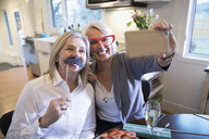 Playful senior women friends wearing fake mustache taking selfie - HEROF31210