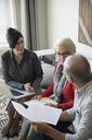 Financial advisor with laptop and paperwork meeting with senior couple in living room - HEROF31285
