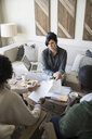 Financial advisor with paperwork meeting with couple in living room - HEROF31288