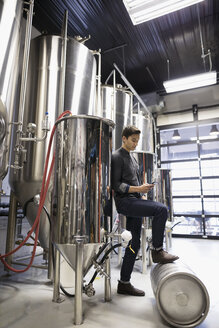 Male brewer using digital tablet near vats in brewery - HEROF31312