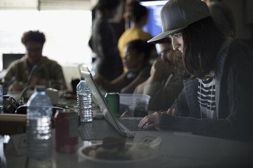 Focused female hacker wearing baseball cap working hackathon at laptop in dark office - HEROF31345