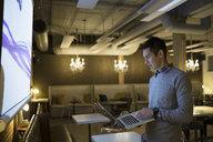 Focused businessman using laptop preparing audio visual presentation in office - HEROF31381