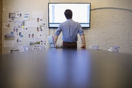 Male designer watching television monitor in conference room - HEROF31402