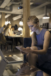 Focused businesswoman working at digital tablet and laptop in office - HEROF31408