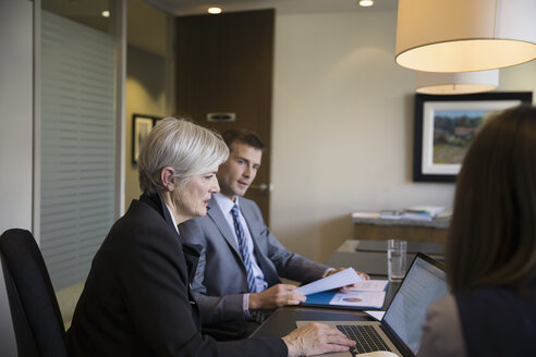 Lawyers talking and working at laptop in conference room meeting - HEROF31441